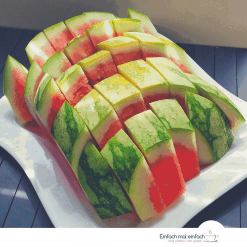 Watermelon cut in sticks on white square plate and dark wooden ground.