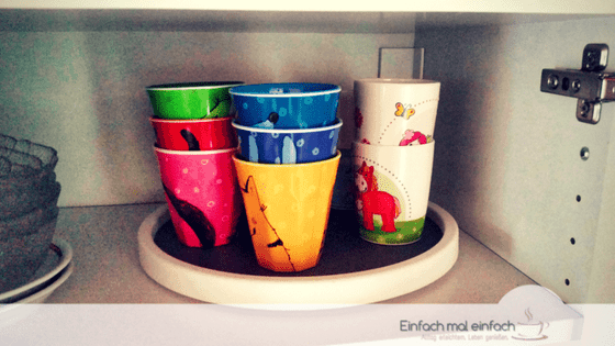 Colorful kids cups arranged on a Lazy Susan in a cupboard.
